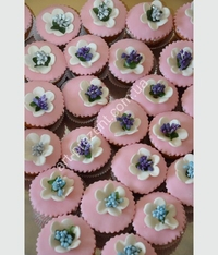 Muffins pink with flowers. Wonderful and tasty buffet table decoration. Possible, chocolate, cream, caramel, and other toppings. Minimum quantity 6 PCs.